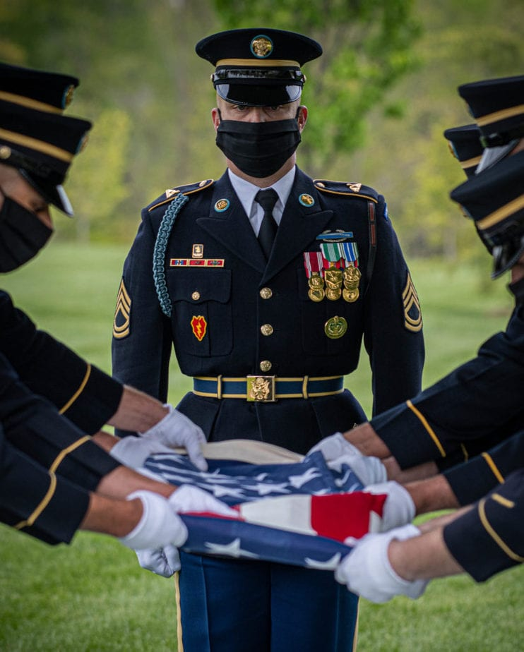 Member of the US Army Old Guard fold a flag during a service at Arlington National Cemetery during the COVID pandemic | arlington funeral service | Arlington Media, Inc.